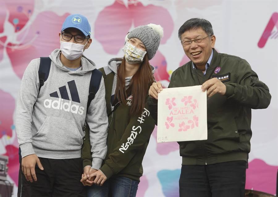 2020台北杜鵑花季正式開跑,台北市長柯文哲(右)14日現身大安森林公園的杜鵑花音樂會,親手絹印杜鵑花帆布袋,送給現場一對情侶。(張鎧乙攝)