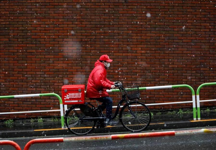 大阪業者推出「日人專用樓層套餐」挨轟,被迫下架。因為疫情,許多民眾不敢出門。圖為東京的食物外送員載口罩送餐。(路透)