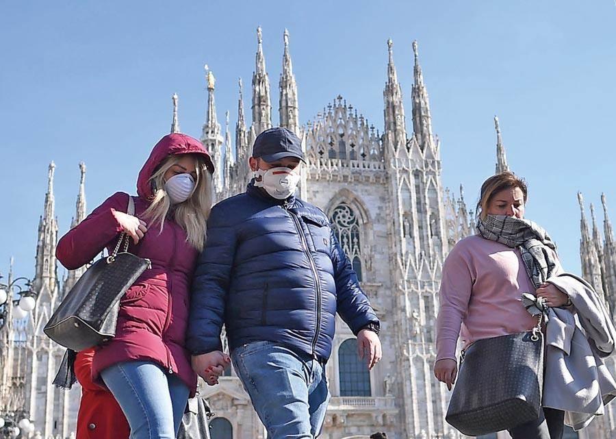 義大利疫情失控。圖為民眾戴口罩走過米蘭大教堂。(新華社)