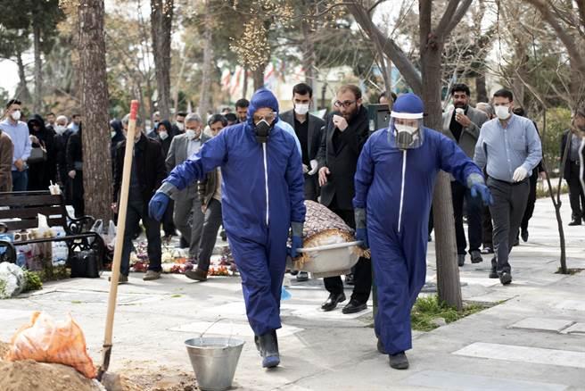 圖為穿防護裝的伊朗男子抬著德黑蘭議員法特梅赫·拉巴爾的屍體預備進行埋葬。該議員在德黑蘭郊外的貝謝特·埃·扎赫拉墓地感染了新的冠狀病毒後死亡。伊朗當局已要求新冠病毒死者的親友盡量不要參加葬禮,以免感染病毒。(圖/美聯社)