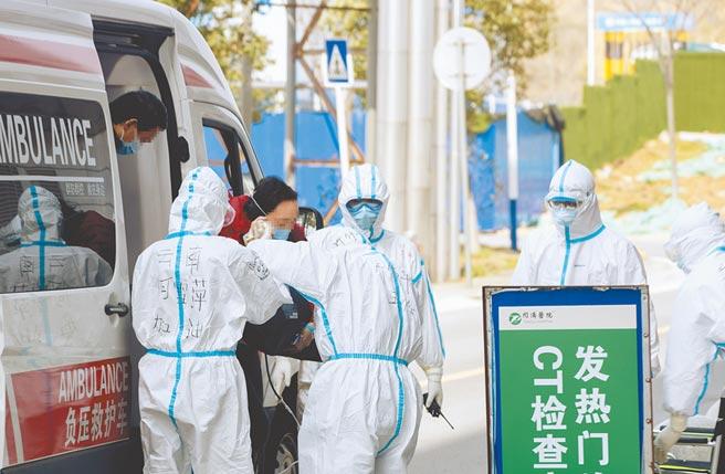 3月14日,在同濟醫院光谷院區,「擺渡人」(前左)和醫護人員一起幫一名老年患者下車。(新華社)
