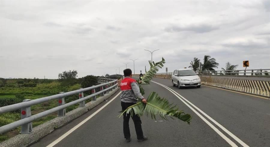 民眾揮舞香蕉葉協助提醒車輛注意繞道。(翻攝照片/楊漢聲台東傳真)