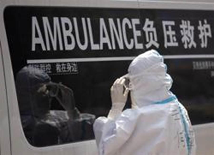 3月14日,「擺渡人」小分隊隊員何雪萍在武漢對著救護車車窗查看護目鏡佩戴情況。(照片取自新華社)