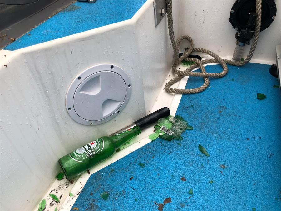 海巡快艇的甲板上,仍可見陸船丟擲的酒瓶和碎片。(李金生攝)