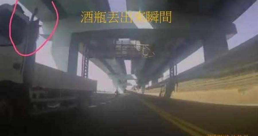 外送員騎重機上快速道路,卻遇上大型卡車惡意逼車,司機還朝他丟擲酒瓶。(圖/翻攝畫面)