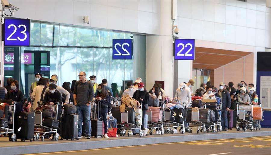 排隊搭乘防疫計程車的入境旅客排隊人龍超過上百公尺,,搭上車要等待近二小時。(資料照,陳麒全攝)