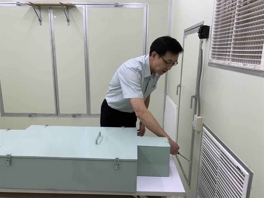 勤益科大冷凍空調與能源系主任吳友烈在模擬負壓病房內檢測氣流方向。(林欣儀攝)