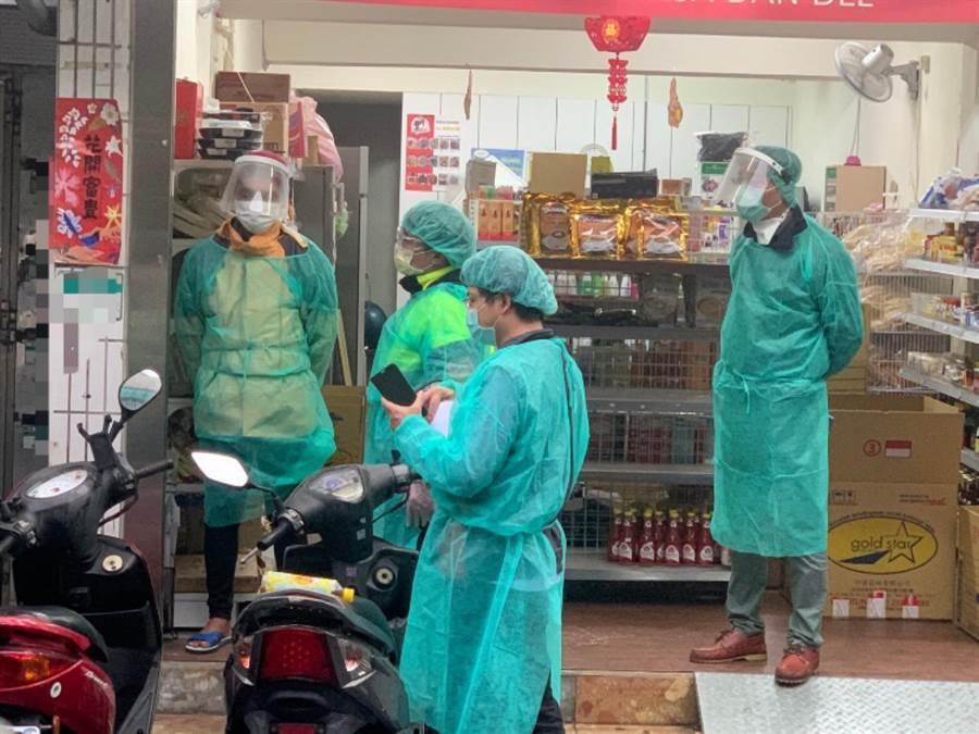 穿著防護裝備的警方,在雜貨店逮捕逃逸外勞(左一)。(民眾提供/陳鴻偉台北傳真)