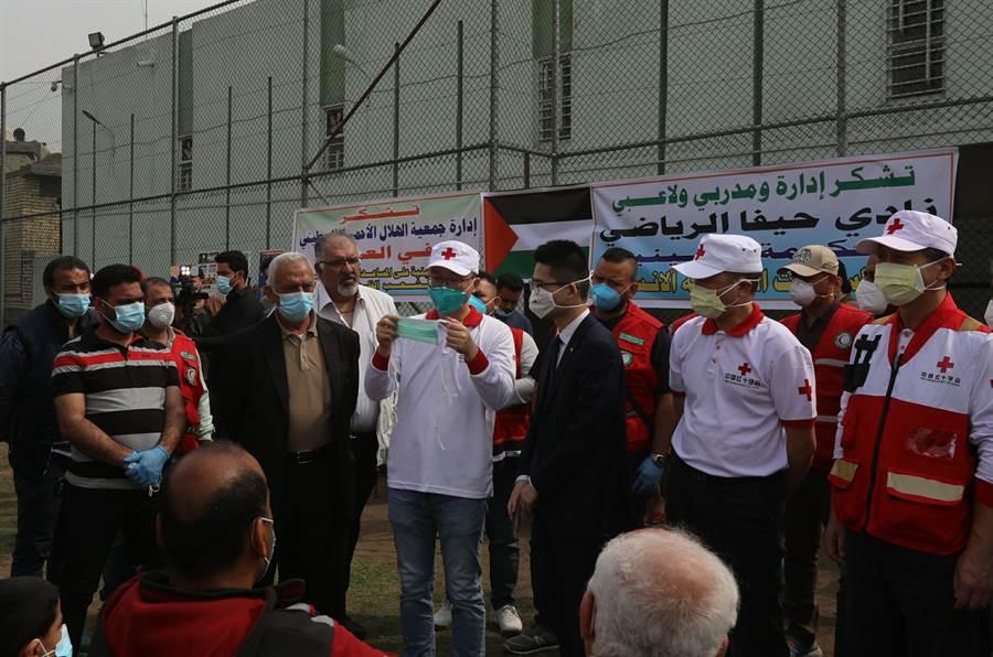 3月16日,在伊拉克巴格達東部的海法巴勒斯坦社區活動中心,大陸專家演示口罩佩戴方法。(新華社)