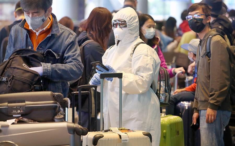 在桃園機場第二航廈外,1名身穿防護衣的旅客,正在排隊等候防疫計程車。(范揚光攝)