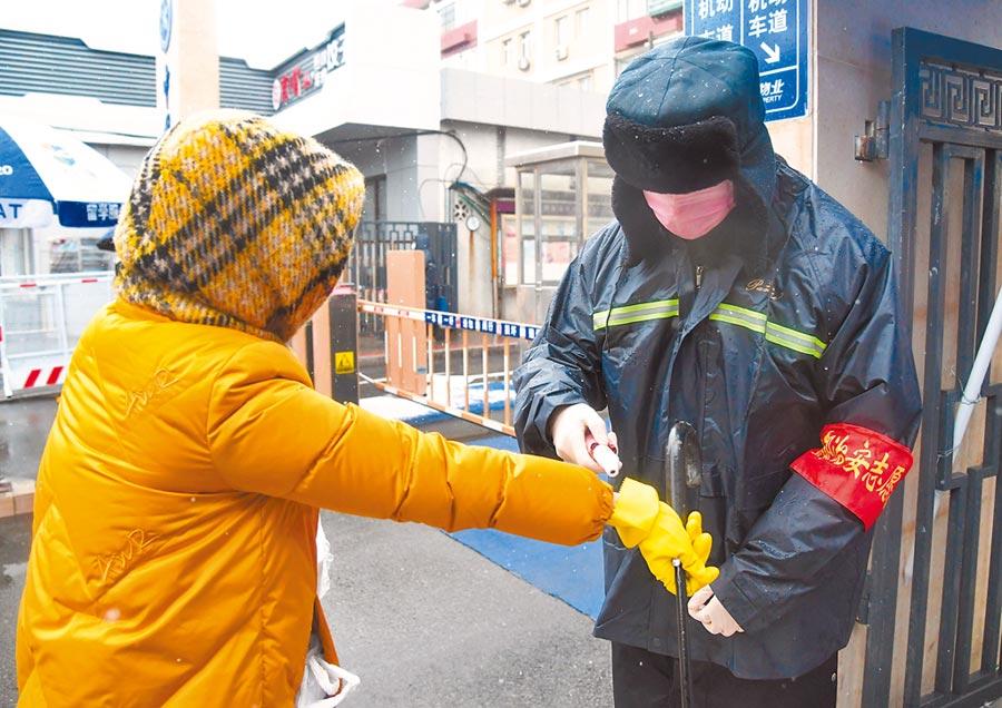 2月14日,北京海淀區中關村街道黃莊社區工作人員(右)在為社區居民測量體溫。(新華社)