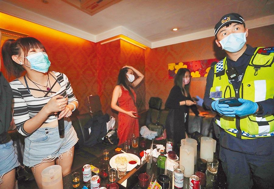 新北市政府22日實施公安防疫擴大臨檢,警察在板橋區「星據點KTV」查驗消費者身分,檢查是否有未落實居家檢疫之民眾及尚未返國之外國旅客到店裡消費。(劉宗龍攝)