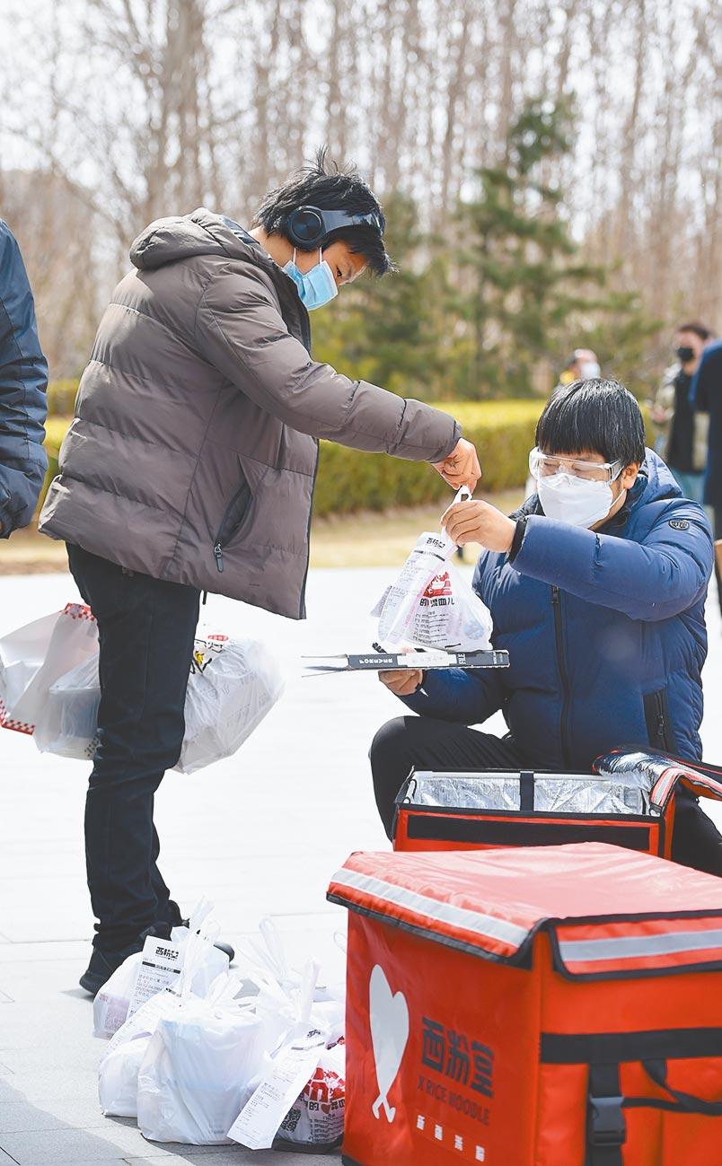 午餐高峰時段,北京一名餐飲商家員工將外賣交給一名送餐員。(中新社資料照片)