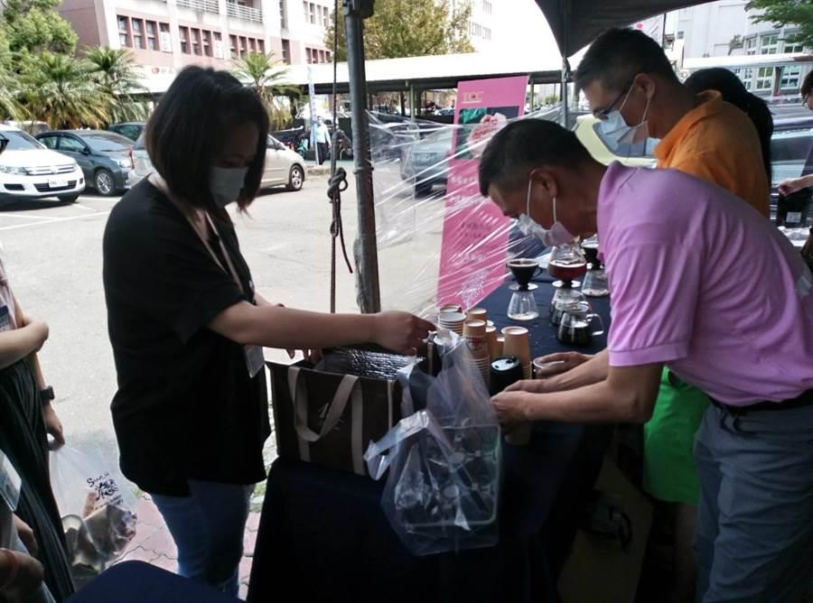 雲林咖啡業者徐飴鴻(右)為向前線防疫醫護致敬,24日在台大醫院雲林分院外設置暖心咖啡小站,現沖咖啡慰勞醫護人員。(許素惠攝)