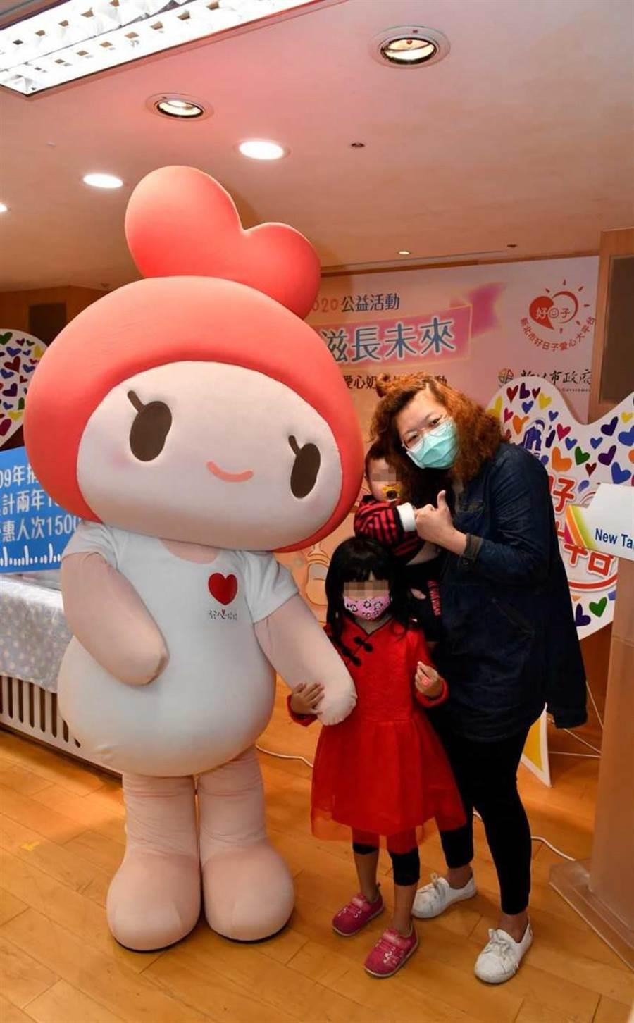 受贈家戶代表的小朋友開心地挽著協會公益大使發心娃娃的手,一同合影留念。(圖/道家人文協會提供)
