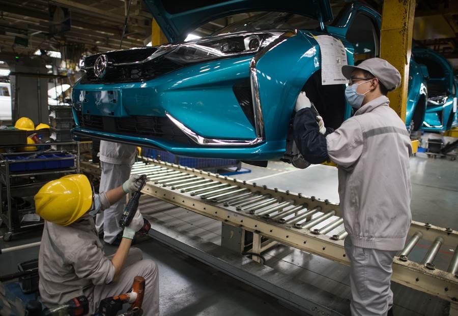 武漢各企業開始陸續復工復產,24日在東風乘用車公司工廠總裝車間的流水線上,工人們加緊生產。(新華社)
