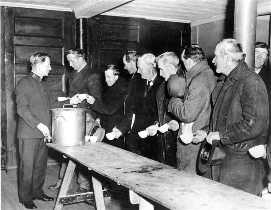 1930年代美國經濟大蕭條時期,民眾排隊領取救世軍分發的免費食物。(美聯社)