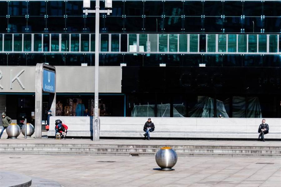 3月23日,在德國首都柏林的亞歷山大廣場,人們在休息時保持距離。(新華社照片)