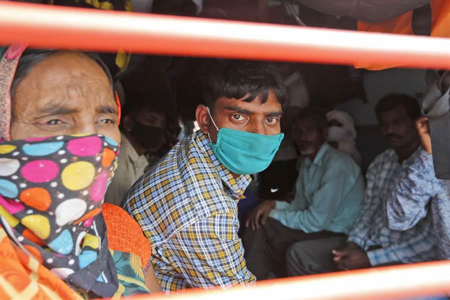 印度宣布鎖國21天。圖為民眾戴口罩搭車。 (圖/美聯社)