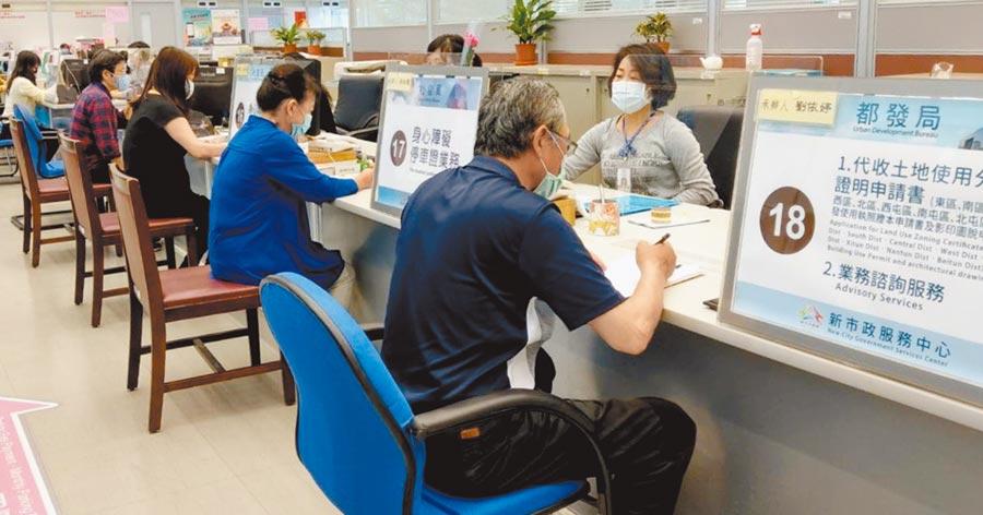 台中市府服務中心設置透明壓克力隔板,文件從隔板上方遞送,隔絕口沫傳染。(盧金足攝)