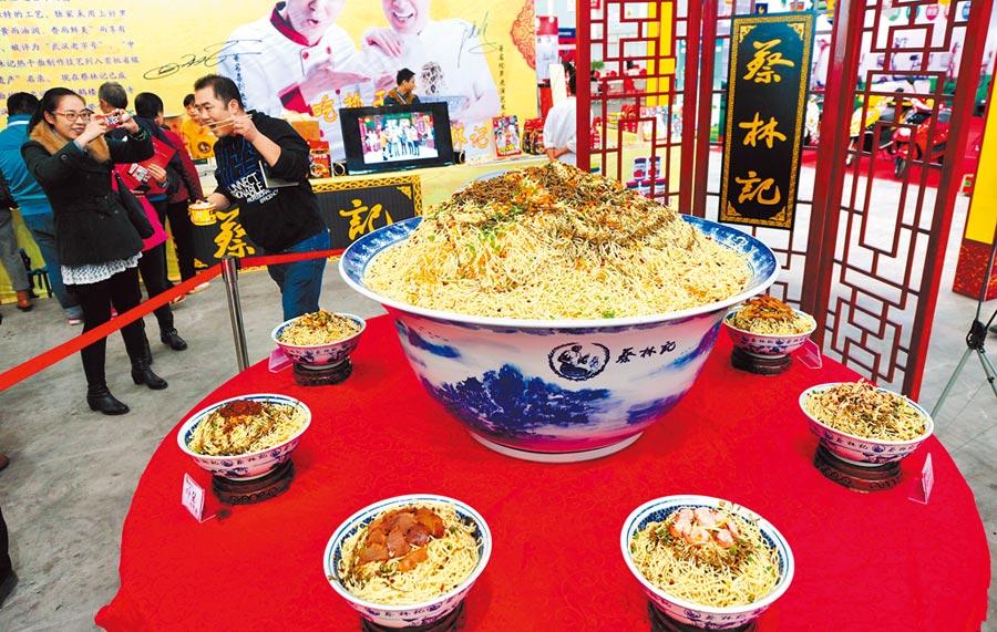 熱乾麵是武漢知名小吃,圖為第二屆武漢國際時尚博覽會展示「中國第一大碗熱乾麵」吸引參觀者。(中新社資料照片)