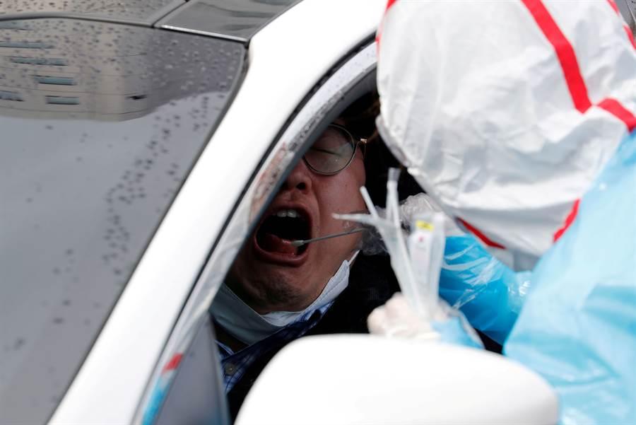 韓國大量製造病毒檢測盒,普遍對所有可能感染者實施病毒檢測,甚至開設不下車檢測站,只要10分鐘就能完成,6小時結果出爐,目前已有30萬人受檢。(圖/路透)