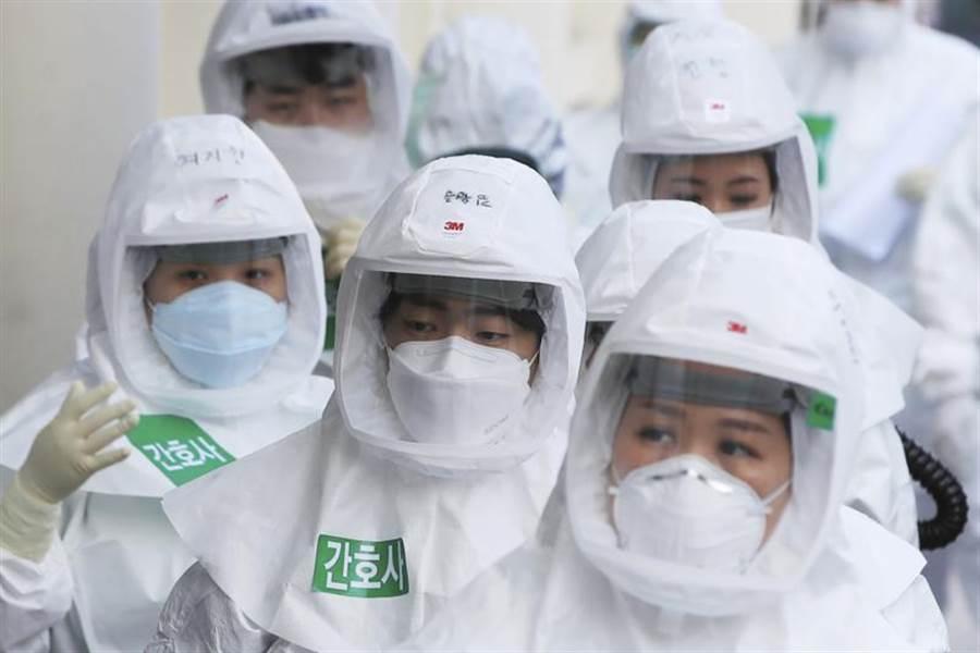 韓國曾是中國大陸以外新冠疫情最嚴重的國家,但目前每日新增確診人數控制在10人以下,許多國家的專家認為應該學習韓國的經驗,已開始派人向韓國取經。圖為著防護裝的韓國醫務人員。(圖/美聯社)