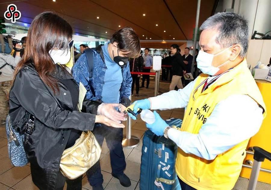 圖為桃園機場防疫車隊以酒精為旅客消毒雙手。(圖/本報系資料照)