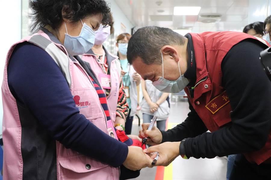 新北市長侯友宜今前往新莊衛生所慰問,熱情同仁要求簽名。(吳亮賢攝)