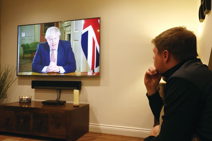 圖為英國民眾觀看首相強生發表電視演說,下令全國封城,此措施至少將持續三周。圖/路透