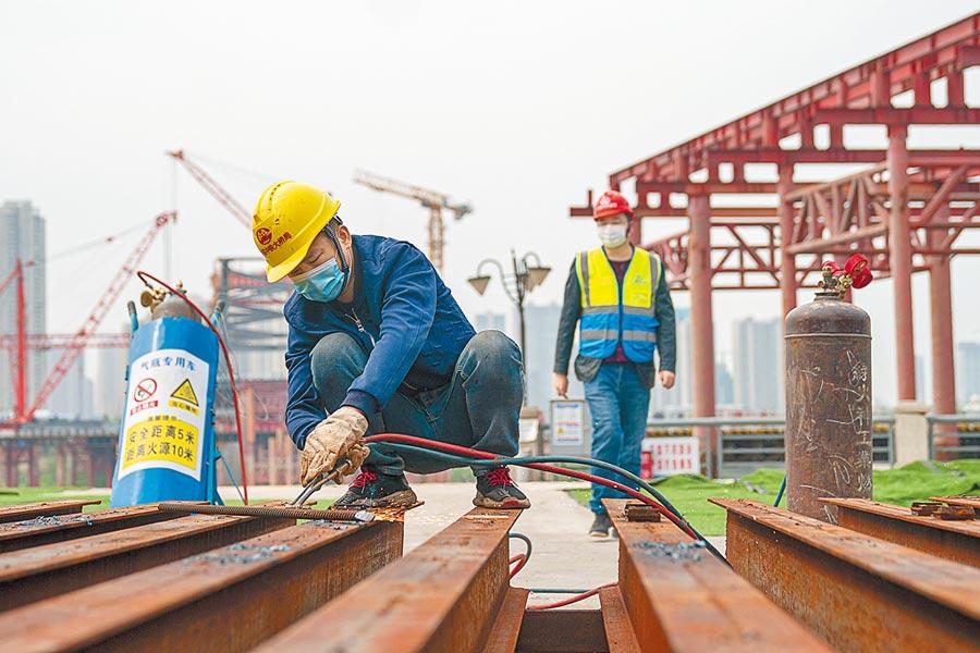 3月24日,武漢江漢七橋建設項目復工,施工人員正在作業。(新華社)