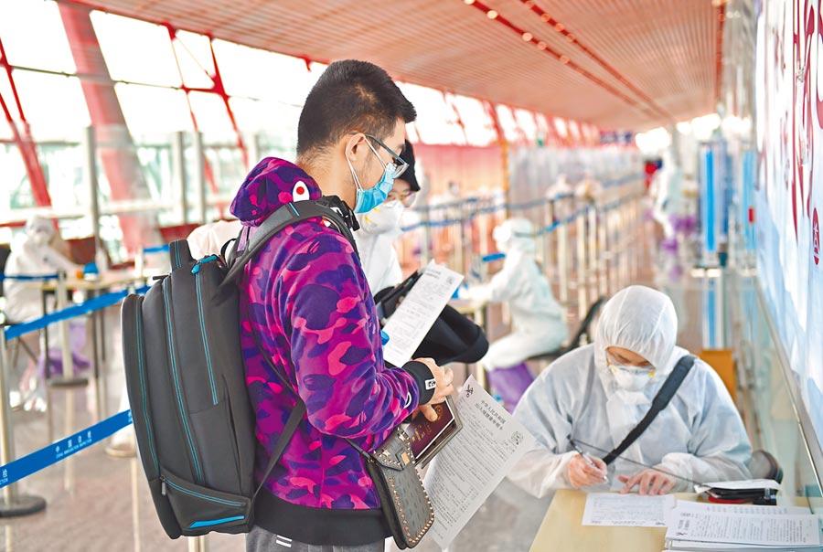 3月21日,北京首都國際機場的入境旅客填寫健康申明卡。(新華社)