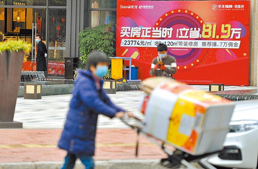 3月5日,福州市民從一房地產「買房正當時」的廣告旁經過。(中新社)