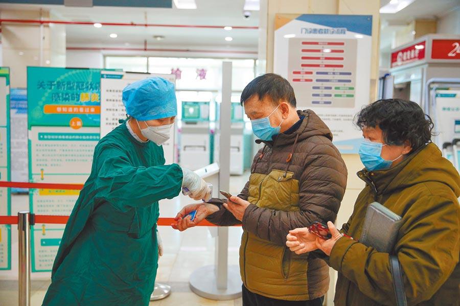 3月19日,在中國醫科大學附屬第四醫院門診部,醫護人員為入院民眾測量體溫。(新華社)