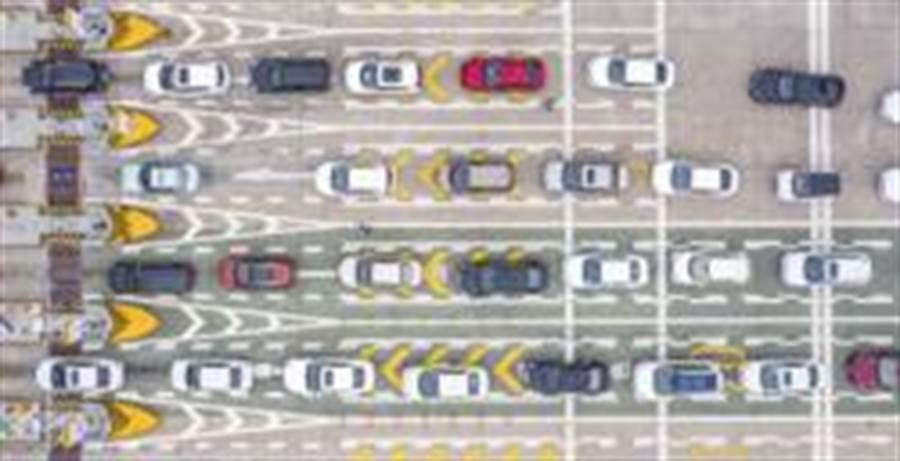 武漢市4月8日起解除離漢離鄂通道管控措施。3月24日,在武漢西高速收費站交通卡點,返漢車輛排隊等候入城。(照片取自新華社)