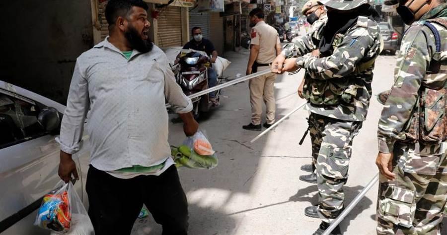 一名男子外出採買民生用品,被警方拿警棍揮舞。(圖/路透社)
