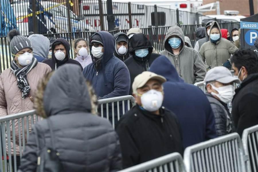 病患25日戴著口罩,在紐約醫院外大排長龍,等著接受新冠肺炎檢測。(美聯社)