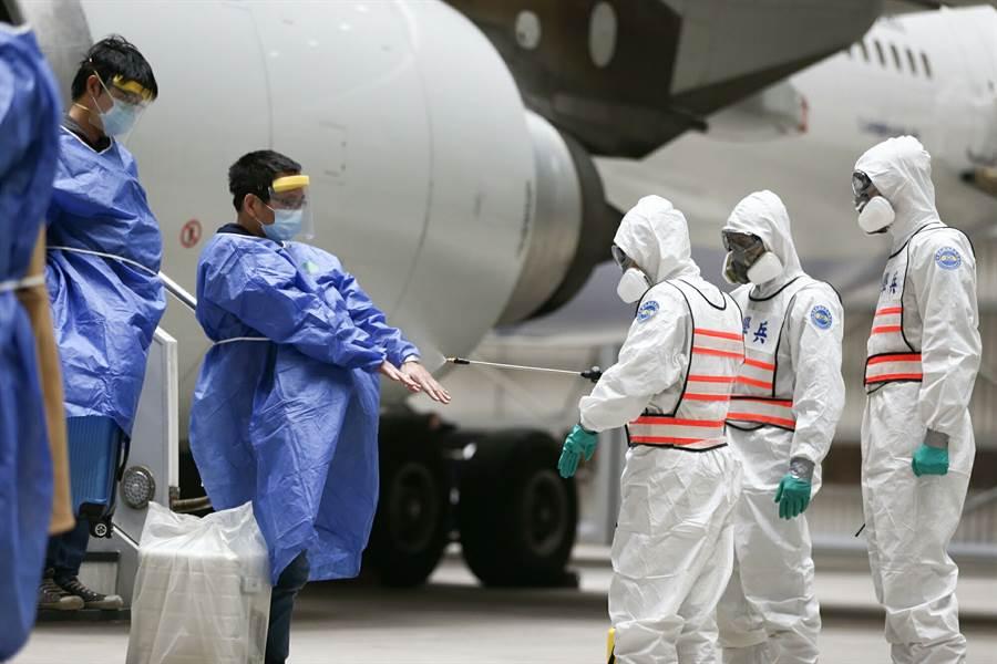 3月11日,滯留湖北武漢的國人搭乘第二批包機返抵桃園國際機場,國軍化學兵部隊為返國的乘客們進行第一道消毒作業。(軍聞社)