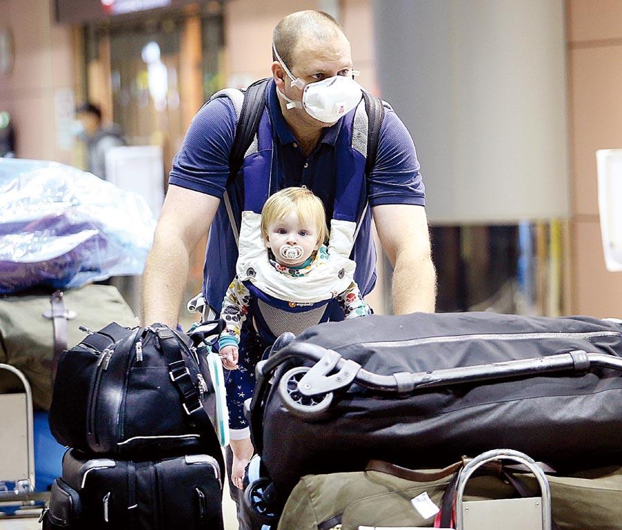 新冠肺炎疫情在全球擴散,台灣案例仍在上升。專家認為,當初對歐美日升級太慢,圖為外籍旅客帶著孩子準備搭車離去。(范揚光攝)