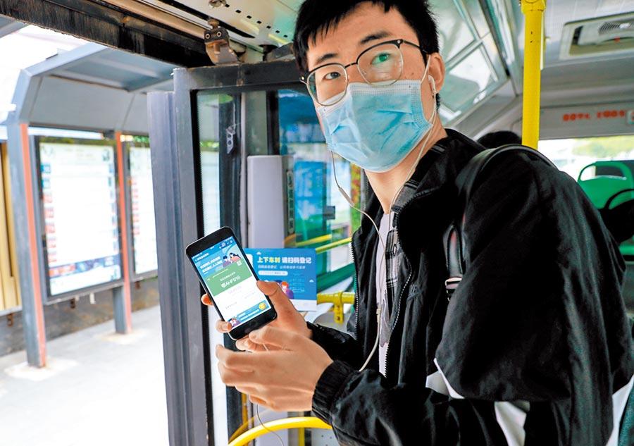 武漢部分公車路線25日恢復營運,圖為市民到站時用手機掃碼後下車。(中新社)
