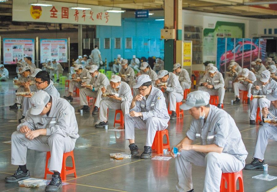 企業復工,武漢一廠內工人們保持兩公尺距離吃午飯。(新華社資料照片)