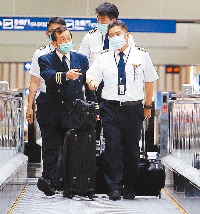 各航空公司為因應疫情嚴訂相關規範,圖為4名戴著口罩的機師準備登機值勤。(本報資料照片)