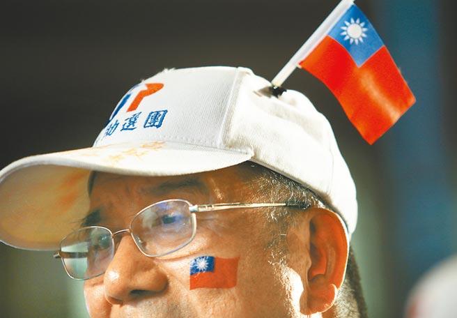 民眾臉上貼上國旗貼紙外,帽子也別上小國旗。(陳怡誠攝)