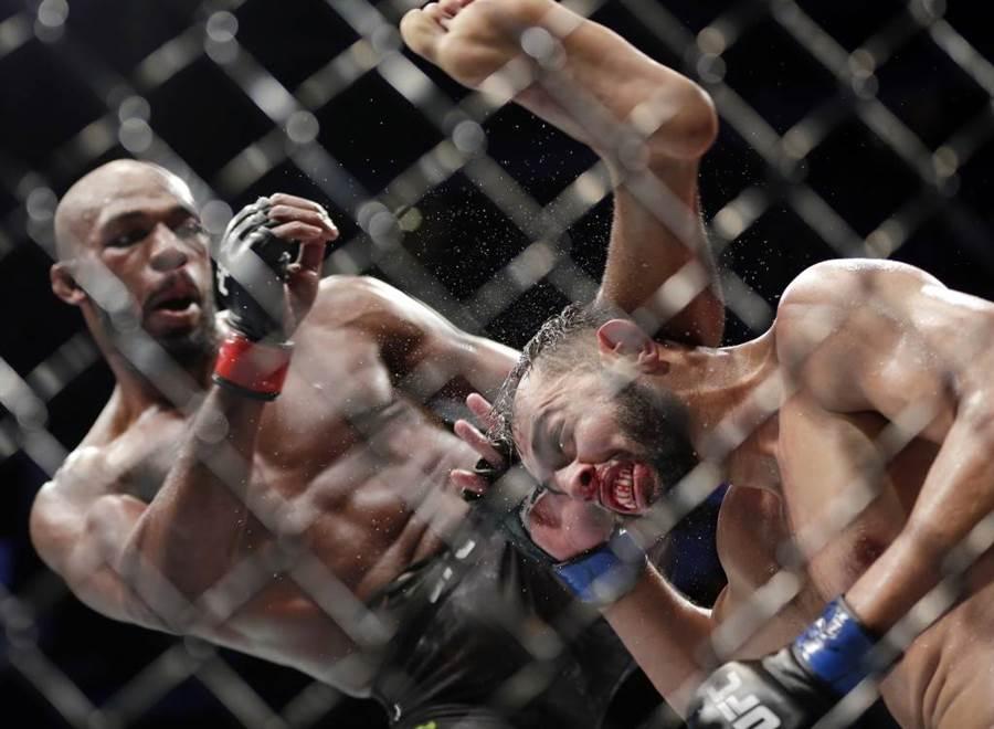 UFC輕重量級拳王瓊斯(左)舉腳要踢對手的頭。(美聯社資料照)
