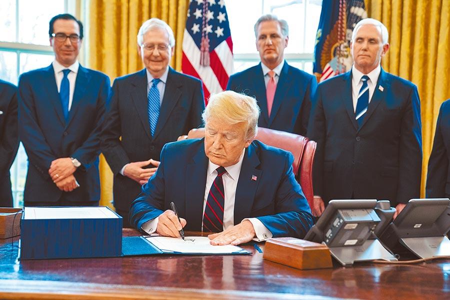 美國總統川普27日在副總統彭斯和國會共和黨領袖等人注視下,簽署2.2兆美元的經濟刺激法案。(美聯社)