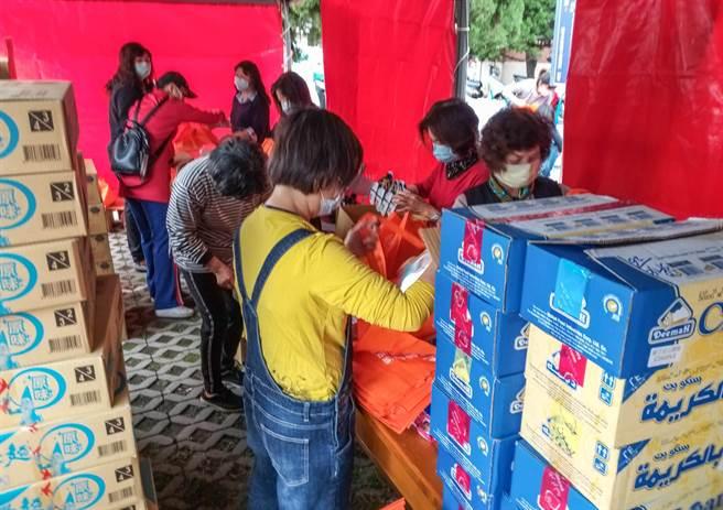 竹北市公所前廣場30日搭棚,由醫友協進會20多名志工在防疫包內加裝泡麵和餅乾。(羅浚濱攝)