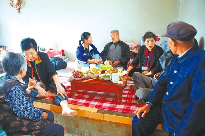 2005年,當年杭州知青插隊多年,回銀川和當地群眾圍坐炕頭道家常。(新華社)