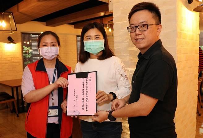 嘉義市衛生局、觀新處官員提供飯店業者通過餐飲衛生檢核公告,讓業者張貼。(廖素慧攝)