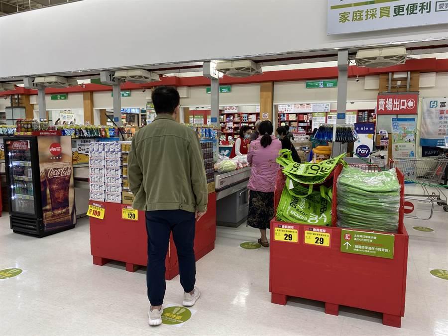 愛買在結帳區設置1.5公尺的綠色地貼,指引民眾等候結帳時,要維持1.5公尺的防疫社交距離。(蔡依珍攝)