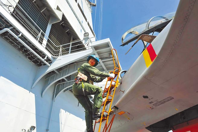 大陸飛行員駕駛殲-15艦載戰鬥機在遼寧艦上進行阻攔著艦和滑躍起飛。圖為飛行員出艙。(中新社資料照片)